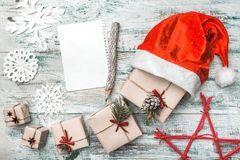 Old wooden white background. Let`s go to Santa. Christmas greeting card, Handmade items. Many gifts artistically arranged. His Santa`s hat. Pencil. Xmas and Stock Photography
