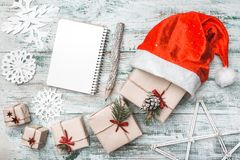 Old wooden white background. Let`s go to Santa. Christmas greeting card, Handmade items. Many gifts artistically arranged. His Santa`s hat. Xmas and Happy New Stock Photography