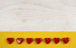 Old wooden white background with seven red hearts on the yellow Stock Images