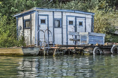 Old Wooden White-Blue Raft Weekend House On Sava River - Belgrade - Serbia. Photograph of an old, handmade weekend leisure wooden white-blue painted raft hut Royalty Free Stock Photo