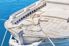 Old wooden white fishing red boat tied on dock. Close Stock Photos