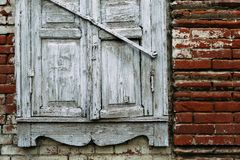 Old wooden white window destroyed by time. Brick wall royalty free stock images
