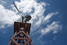 Old Wooden Windmill and Cloudy Sky. An old wooden windmill stands against a cloudy Colorado sky Royalty Free Stock Photography