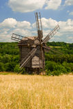 Old wooden windmill on a field, Pyrohiv, Ukraine. Old windmill on the edge of a wheat field, National Museum of Folk Architecture and Life of Ukraine Royalty Free Stock Photo