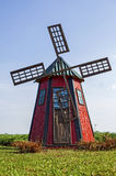 Old wooden windmill painted in red. With blue sky in the background Royalty Free Stock Photography