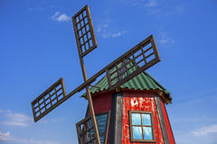 Old wooden windmill. Painted in red, with blue sky in the background Stock Images