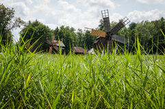 Old wooden windmill seen trough grass Royalty Free Stock Photos
