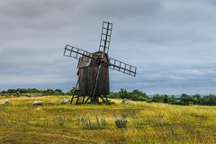 Old wooden windmill standing on a green field by the coast. Of Öland, an island outside the Swedish east coast stock photo