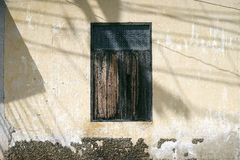 Old wooden window on ancient cement wall with light and shadow,blue vintage filtered image Royalty Free Stock Photo