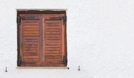 Old wooden window with brown shutters, on rough surfaced wall. royalty free stock photography