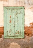 Old wooden window with green shutters on weathered wall. royalty free stock image