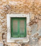 Old wooden window on grunge weathered wall. Old wooden window with green shutters on grunge weathered wall royalty free stock image