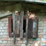 Old rusty wooden hatch in old brick wall stock image