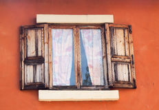 Old wooden window and orange wall Royalty Free Stock Images