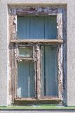 Old wooden window with a vent pane and the remains of white paint on the wall Royalty Free Stock Photos
