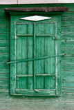 Old wooden window in a wall painte in green color Stock Image