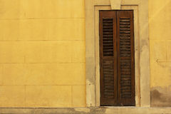 Old wooden window on yellow wall. In Spain village Royalty Free Stock Photo