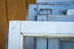 Old wooden windows closeup. Dismantled old wooden windows closeup are made up in a row near the house. white window frames royalty free stock photography