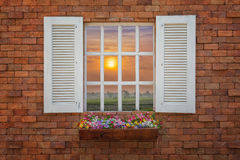 Old wooden windows frame on stone wall and view of sunset royalty free stock photo