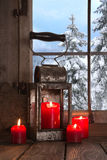 Old wooden windowsill decorated with four red christmas candles. Royalty Free Stock Photos