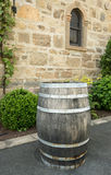 Old wooden wine barrel standing by stone wall of winery. Wooden wine barrel standing by warm stone walls and window of ancient winery in Napa Valley California royalty free stock images