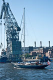 Old wooden yacht and a big crane. Classic wooden yacht near a big floating crane  in the harbor of Saint Petersburg in Russia Stock Photography