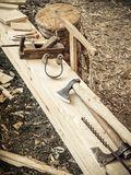 Old woodworking hand tool: wooden plane, chisel ax, and drawing knife in a carpentry workshop on wooden bench ground. Covered with sawdust background side view stock photography