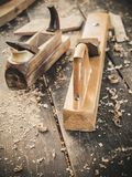Old woodworking hand tool: wooden plane, chisel and in a carpentry workshop on dirty rustic table covered with sawdust royalty free stock image