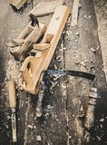 Old woodworking hand tool: wooden plane, chisel and drawing knife in a carpentry workshop on dirty rustic table covered royalty free stock image