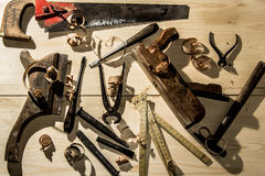 Old woodworks tools: wooden planer, hammer, chisel in a carpentry workshop on wood background stock photography