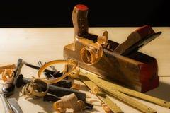 Old woodworks tools: wooden planer, hammer, chisel in a carpentry workshop on wood background stock images
