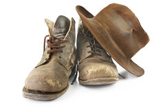 Old Workboots and Hat. Battered old work boots and felt hat, isolated on white.  Used continuously since the 1940's Royalty Free Stock Photography