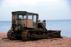 Old worker. Old and rusty bulldozer on a beach Stock Image