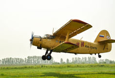 Old worker of An-2. The plane a biplane of small aircraft is on take-off. The plane is in operation since 1948 and still serves all interested structures Stock Photos