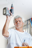 Old worker using drill Stock Images