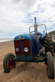 An Old Workhorse. An ancient tractor on a Norfolk beach, used to pull the fishing boats in and out of the water Stock Photo