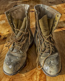 Old working boots. A pair on old working boots on a wooden floor Stock Photo