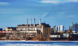 Old working factory, near a water, day, outdoor. Old manufactory in the port, on the background of blue sky. Production of goods near the water Stock Photo