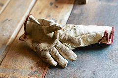 Old working gloves over wooden table, on a metal woodworking machine construction tools stock image