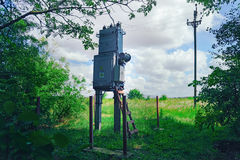 Old working rural electrical distribution transformer in the forest. Sunny day, the concept of industrial. Royalty Free Stock Images