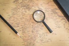 An old world map, a magnifying glass, a pencil and a notepad.  Stock Photo