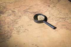 An old world map, a magnifying glass, a pencil and a notepad.  Stock Photos