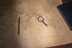 An old world map, a magnifying glass, a pencil and a notepad.  Stock Images