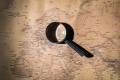 An old world map, a magnifying glass, a pencil and a notepad royalty free stock image