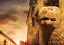 Old world view. Street scenic view of old world Italian boulevard with buildings and focus on old Lion statue in stone with magical sky and golden light royalty free stock photos