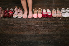 Old worn baby (child, kid) shoes on the floor. sandals, boots, s Stock Photo