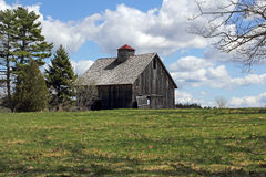 Old worn barn in field with bright cloudy sky Stock Photography