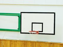 Old worn basketball hoop and  white shool gym wall. Background Royalty Free Stock Image