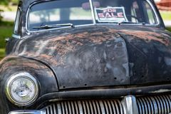 Old and worn beat up car from the forties for sale. Classic old car from the forties, sun burned and worn. For sale in a garden in Sweden stock photo