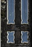 Old and Worn, black and blue door. Old wooden door with faded black, white and blue paint, New Orleans Royalty Free Stock Photo